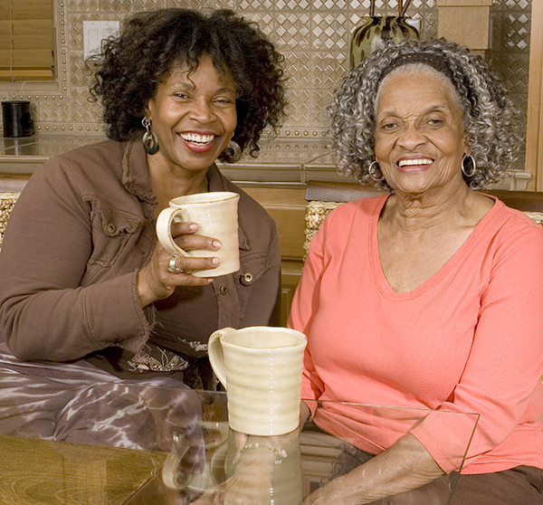 two women sitting with mugs